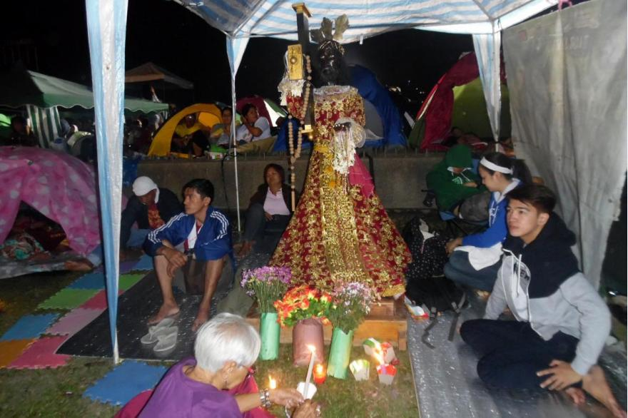 Devotees camp out with their own statue of the Black Nazarene at the overnight vigil preceding the procession. January 8, 2015. Photo by Arnulfo Fortunado.