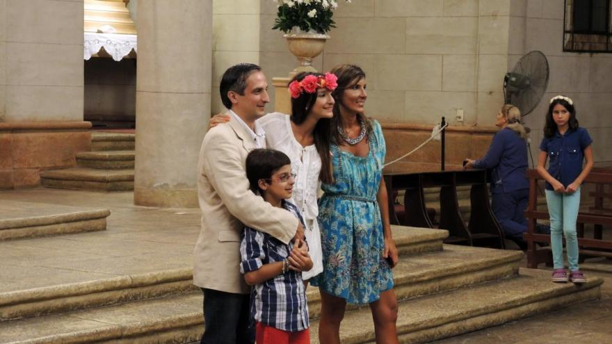 A young woman poses with her family after her quinceañera Mass.