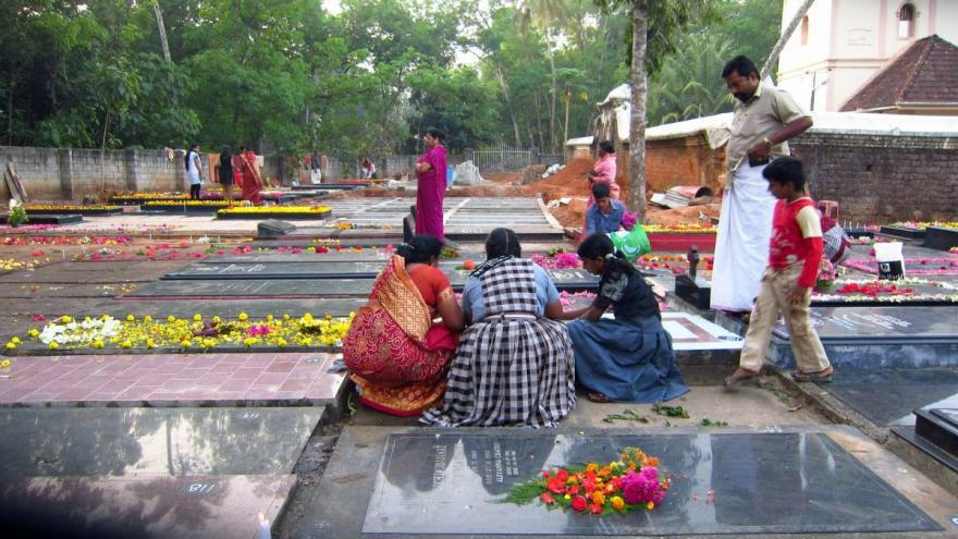Women decorate tombstones before the Day of the Dead procession in India.