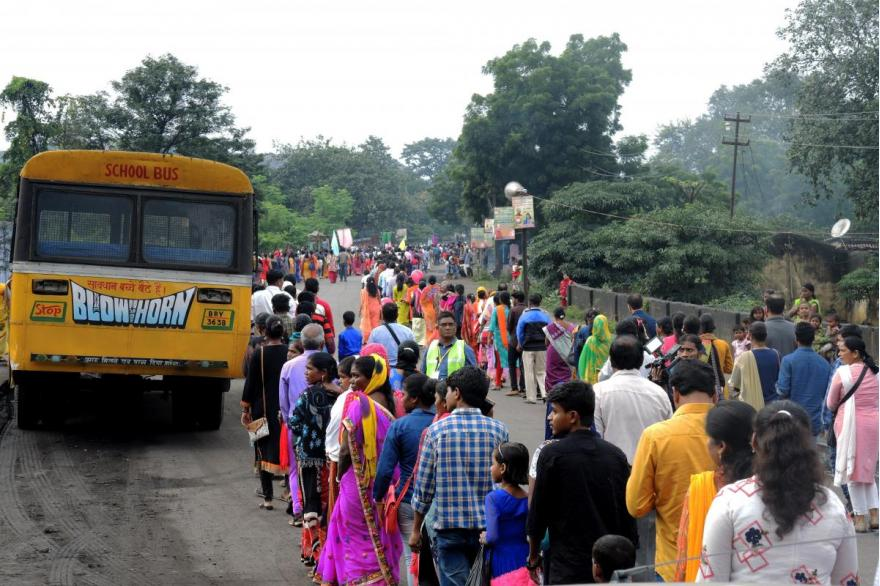 Lines of devotees in procession along a rural road, walk around a yellow bus.